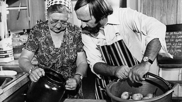 Dans une cuisine, Madame Ernest Dubé, pomicultrice de Rougemont, et l'animateur Jacques Houde sont devant une planche de travail sur laquelle sont posés une cruche et un panier de pommes.