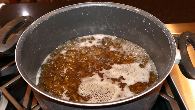 Le riz sauvage cuit dans un gros chaudron.