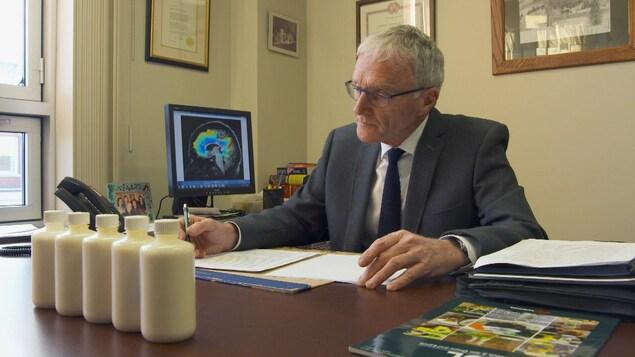 On voit M. Cunnane assis à son bureau, en train de lire des documents. Devant lui sont posées cinq bouteilles remplies d'un liquide blanc.