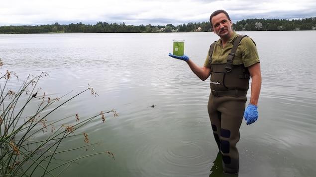 Le professeur Sébastien Sauvé nous montre un bocal d'eau verdâtre aux abords du Petit lac Saint-François.