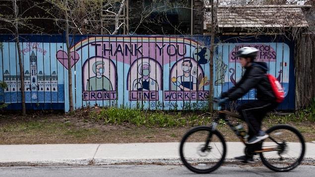 Un cycliste passe devant une murale où il est écrit : Merci aux travailleurs de première ligne.