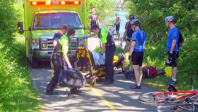Des ambulanciers paramédicaux interviennent sur le sentier des Voyageurs, près de l'Université du Québec en Outaouais, après qu'un cycliste eut subi des blessures.