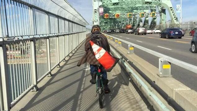 Un cycliste roule sur la piste multifonctionnelle du pont Jacques-Cartier, entre l'île de Montréal et la Rive-Sud.