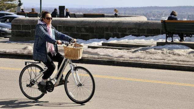 Une cycliste profite du beau temps sur les plaines d'Abraham.