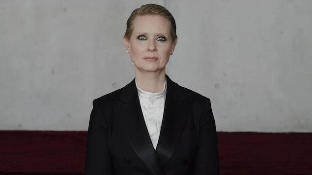 Cynthia Nixon porte une veste noire, une chemise blanche et ses yeux verts sont maquillés de noir.
