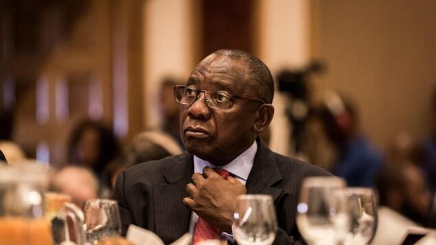 Cyril Ramaphosa, assis à une table, arrange sa cravate.