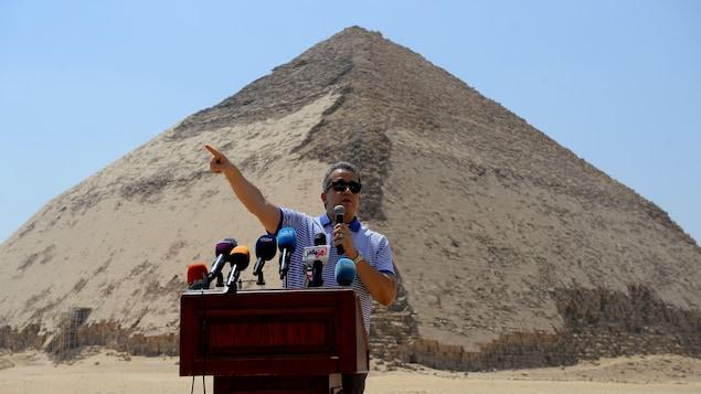 Le ministre parle dans un micro derrière un lutrin. Derrière lui se dresse une pyramide de pierre.