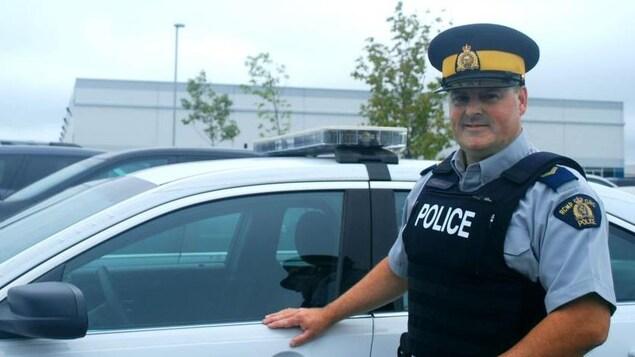 Dal Hutchinson en uniforme de la GRC à côté de sa voiture de patrouille.