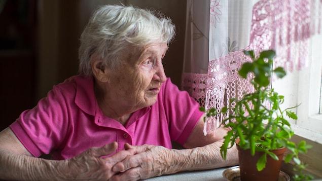 Une dame âgée est assise à une table et regarde par la fenêtre.