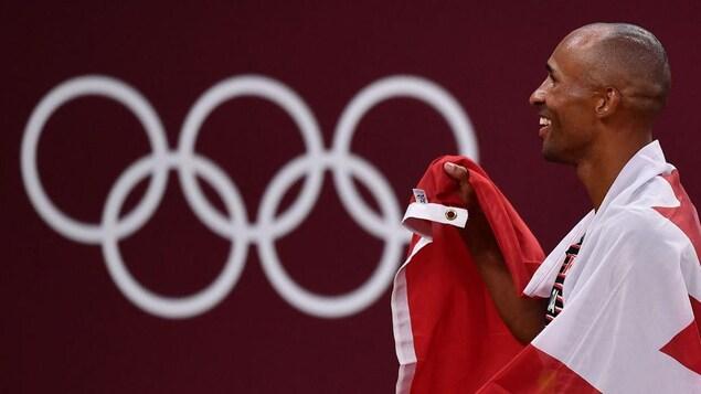 Damian Warner sourit, le drapeau canadien lui couvrant les épaules comme une cape.
