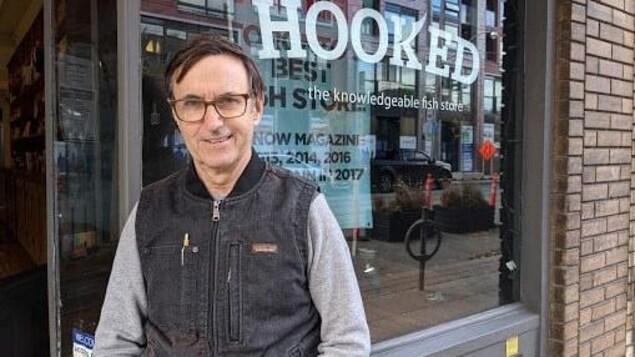 Le portrait d'un homme devant la façade d'un magasin