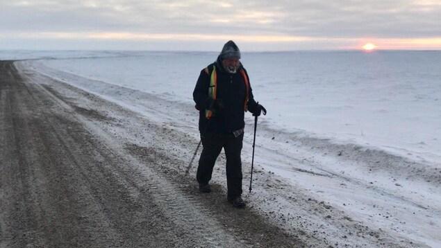 Dana Meise marche dans le froid, bâtons en main, alors que le soleil se couche sur la toundra.