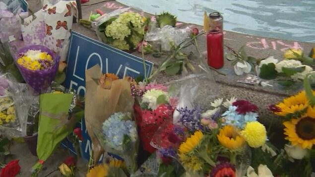 Photo de bouquets de fleurs et d'une bougie le long d'une fontaine