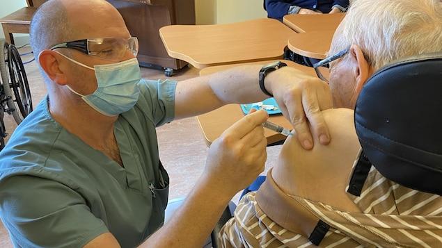 Il administre un vaccin à une personne âgée.