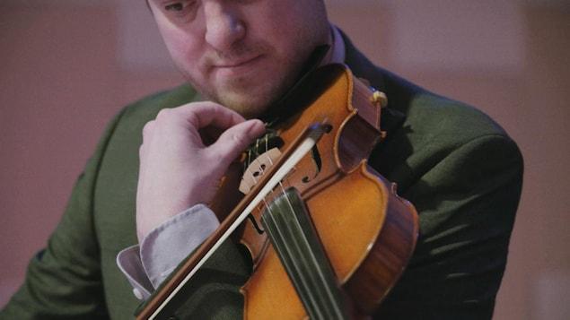 Un musicien tient un violon et un archet.