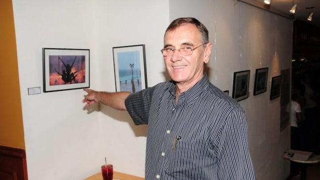 Un homme pointe une photo qu'il a prise.