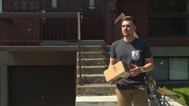 Le jeune homme, un colis dans les mains, devant un immeuble