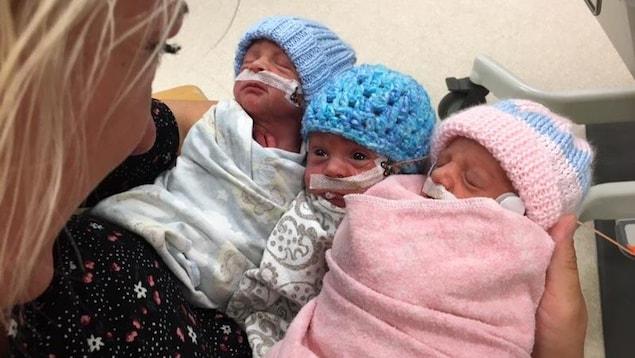 Une mère sourit à ses triplés nouveaux-nés qu'elle tient dans ses bras. Celui du mileu la regarde en retour, les deux autres semblent endormis.