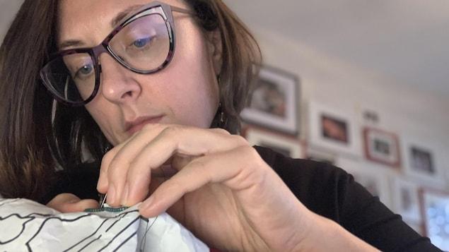 Une femme fait patiemment du perlage dans une pièce avec un mur blanc et des cadres au mur.