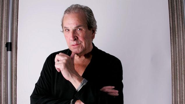 Un homme avec une chemise noire devant un fond blanc utilisé pour la photographie en studio.