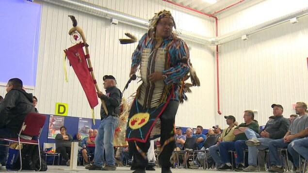 Un homme autochtone en habit traditionnel se produit dans un cercle de danse autochtone, sous l'oeil de douzaines de personnes assises en cercle.