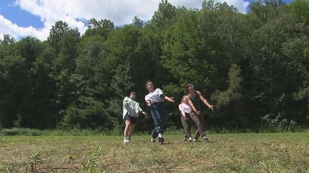 Quatre femmes dansent à l'extérieur.