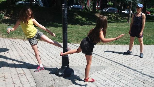 Des jeunes dansent dans un parc sous la supervision de leur animatrice de camp.