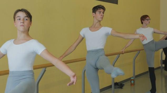 Trois jeunes danseurs de ballet à l'entraînement tiennent la barre d'une main tout en levant un pied dans les airs.