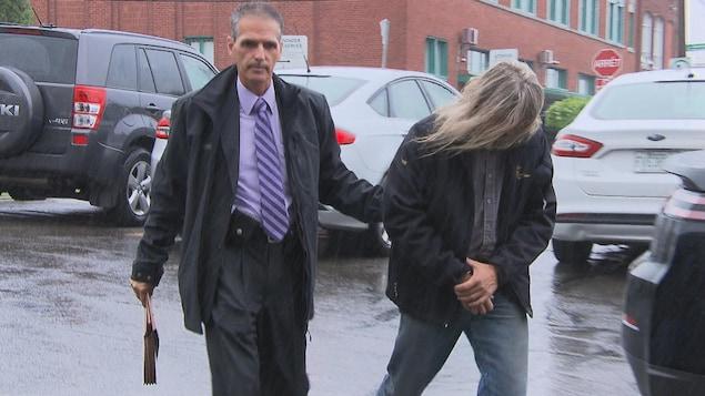 Dany Aubry, la tête baissée, caché par ses cheveux, escorté par un policier dans le stationnement du palais de justice