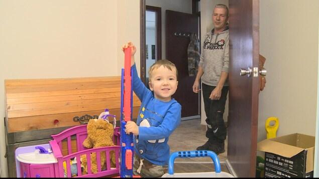 Un enfant joue avec un fusil en plastique. Il a le sourire aux lèvres.