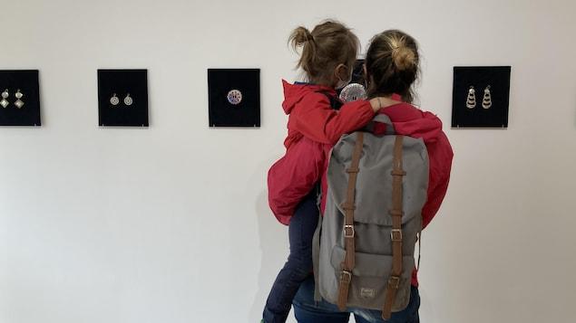 Une mère portant sa fille devant les bijoux exposés de Michel Savard.