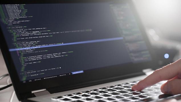 Un homme écrit sur un ordinateur portable.