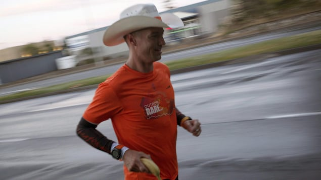Dave Proctor portant un chapeau de cowboy court le long d'une route le jour de son départ le 27 juin 2018 à Victoria