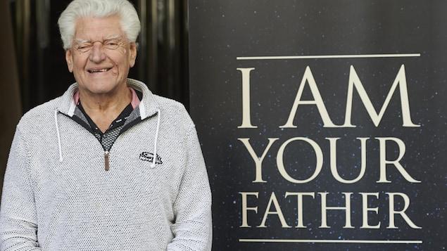 L'acteur devant une affiche où on peut lire la célèbre phrase de son personnage Darth Vader « Je suis ton père » en anglais.