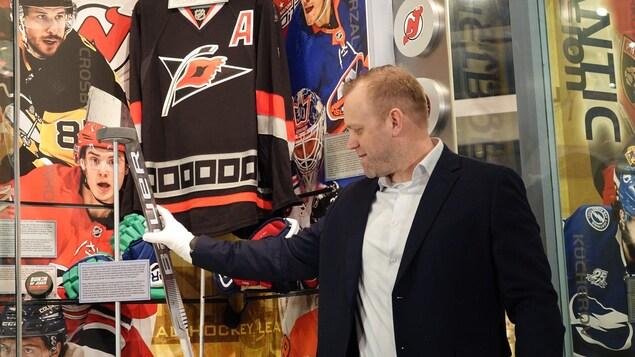 Un homme en veston devant une vitrine avec des objets de hockey.