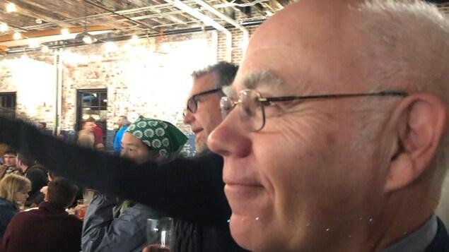 Le chef des verts du Nouveau-Brunswick David Coon regarde les résultats électoraux, sourire aux lèvres.