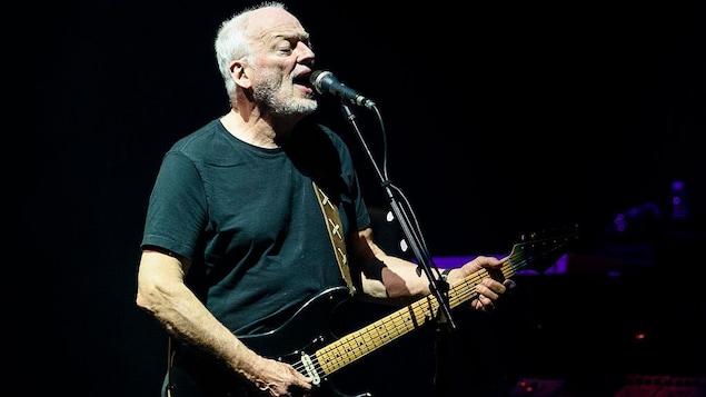 David Gilmour chante et joue de la guitare sur scène