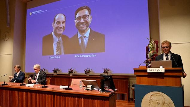Les deux hommes aparaissent sur un écran alors que des membres du comité se trouvent sur la scène.