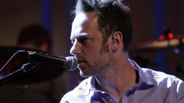 L'homme chante au micro.