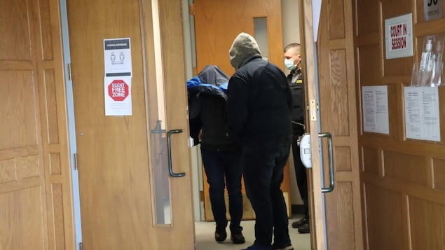 Un homme se couvre de son manteau à la sortie d'une salle d'audience. Il est entouré de deux hommes.