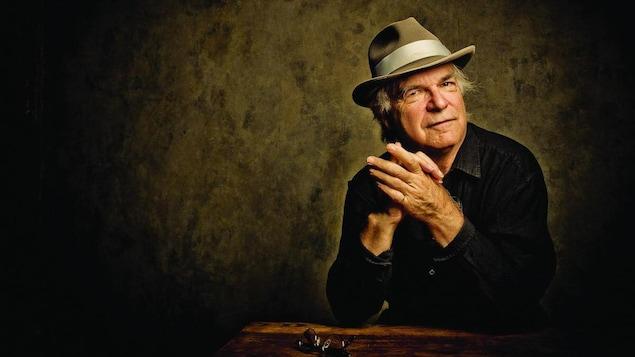 Portrait de David Olney qui porte une chemise noire et un chapeau.