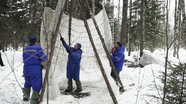 David Saint-Jacques construit une tente avec ses collègues.