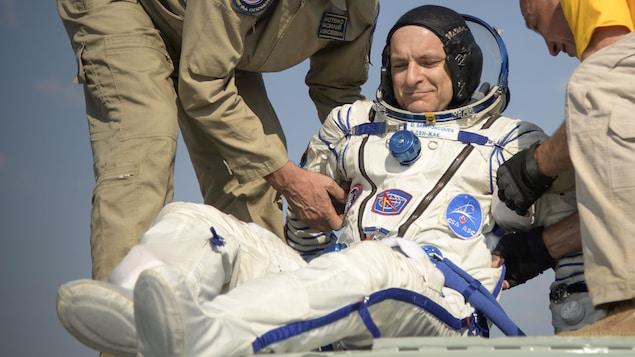 Deux hommes aident un astronaute à sortir d,une capsule spatiale.