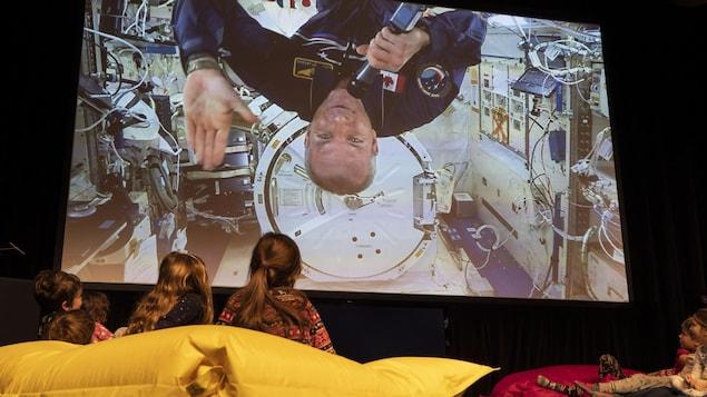 David Saint-Jacques apparaît sur un écran devant des enfants émerveillés.