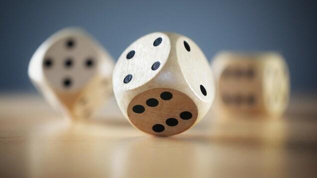 Des dés à six faces en bois sur une table.
