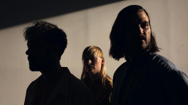 Les 3 membres du groupe, deux hommes et une femme, posent dans la pénombre.