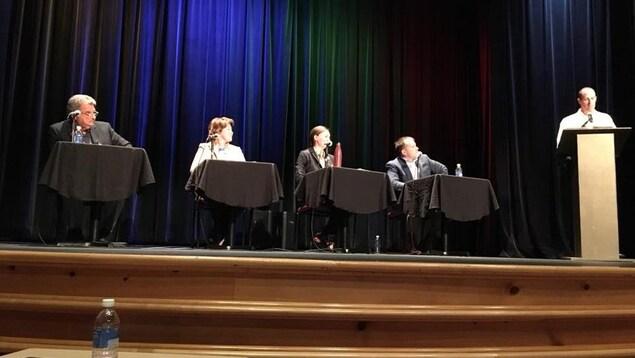 Une photo du débat. Quatre candidats sont près l'un de l'autre dans un auditorium.