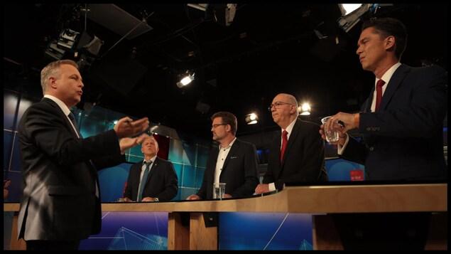 Quatre hommes autour d'une table, sur un plateau de télévision