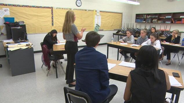 Des élèves sont assis en classe et écoutent une personne en train de parler.