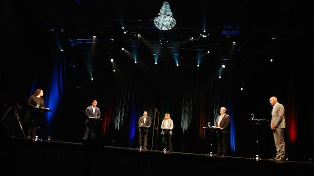 Les candidats se tiennent sur une scène.